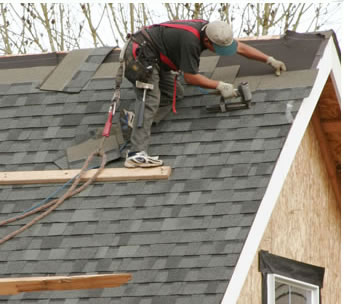 Roofer laying new tile on new construction.