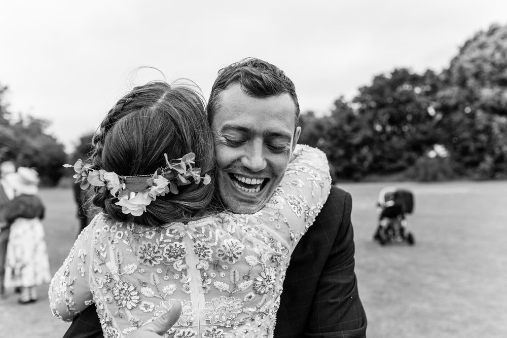 Bride is given a big hug by guest at her wedding