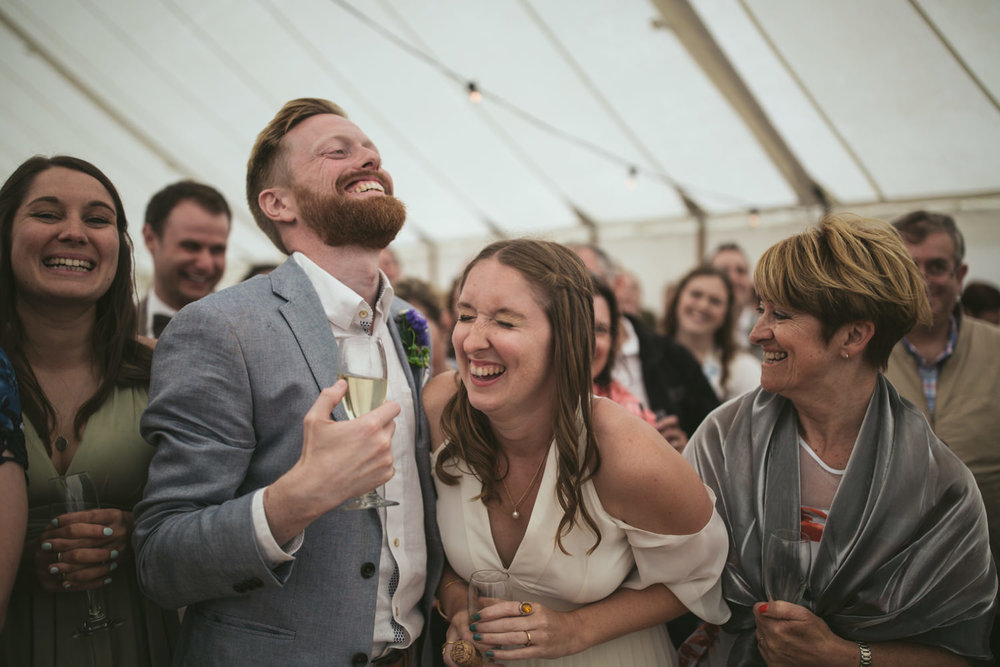 Newly married couple laugh at their reception, in a marquee