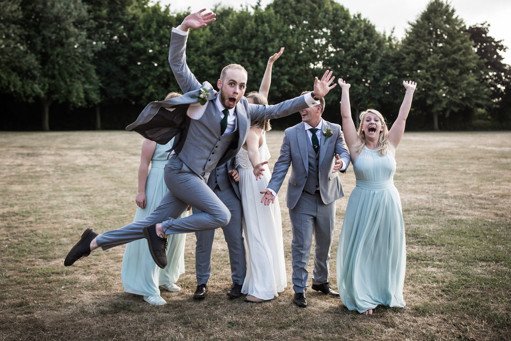 Groom leaps across formal wedding photograph at Mildenhall Suffolk