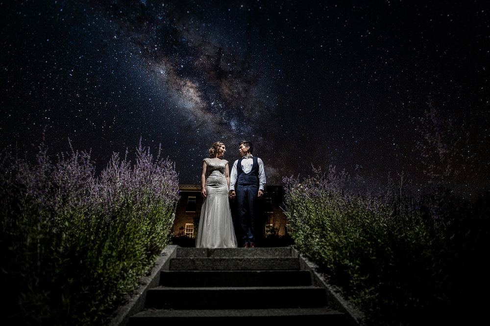 Wedding portrait as couple stand under stars at Headingham Castle