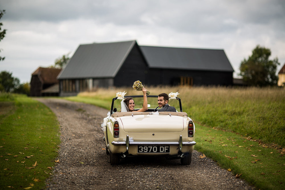 Newly married couple at suffolk barn glance back over their shoulder whilst driving away in a classic car