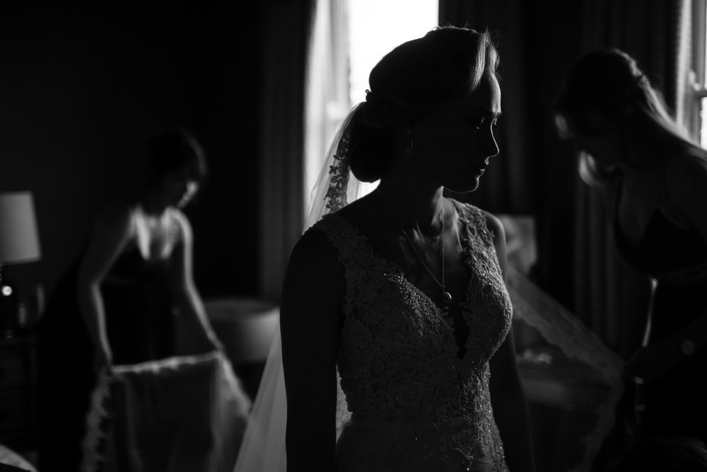 Bride in deep shadow is prepared for her marriage by Bridesmaids