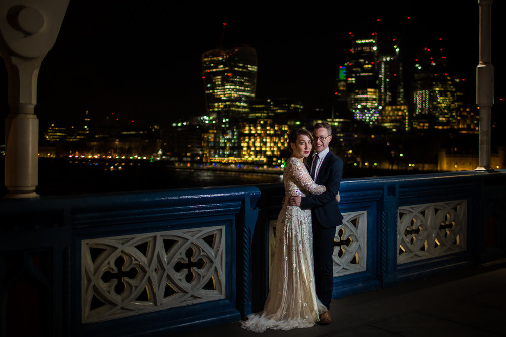 Newly married couple hug on Tower Bridge, London at night