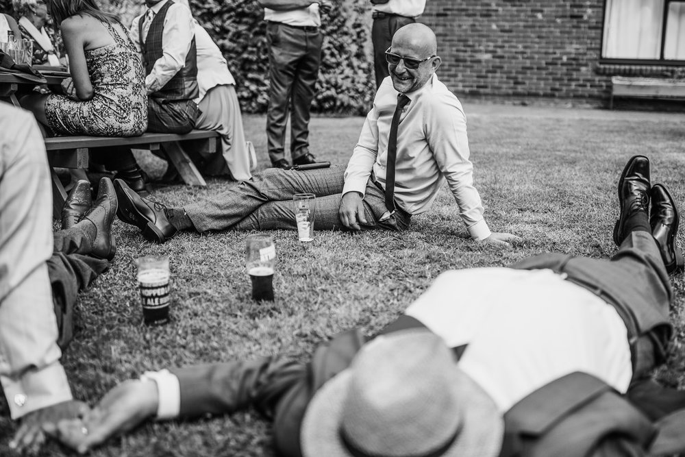 Wedding guests relax on the grass at a reception