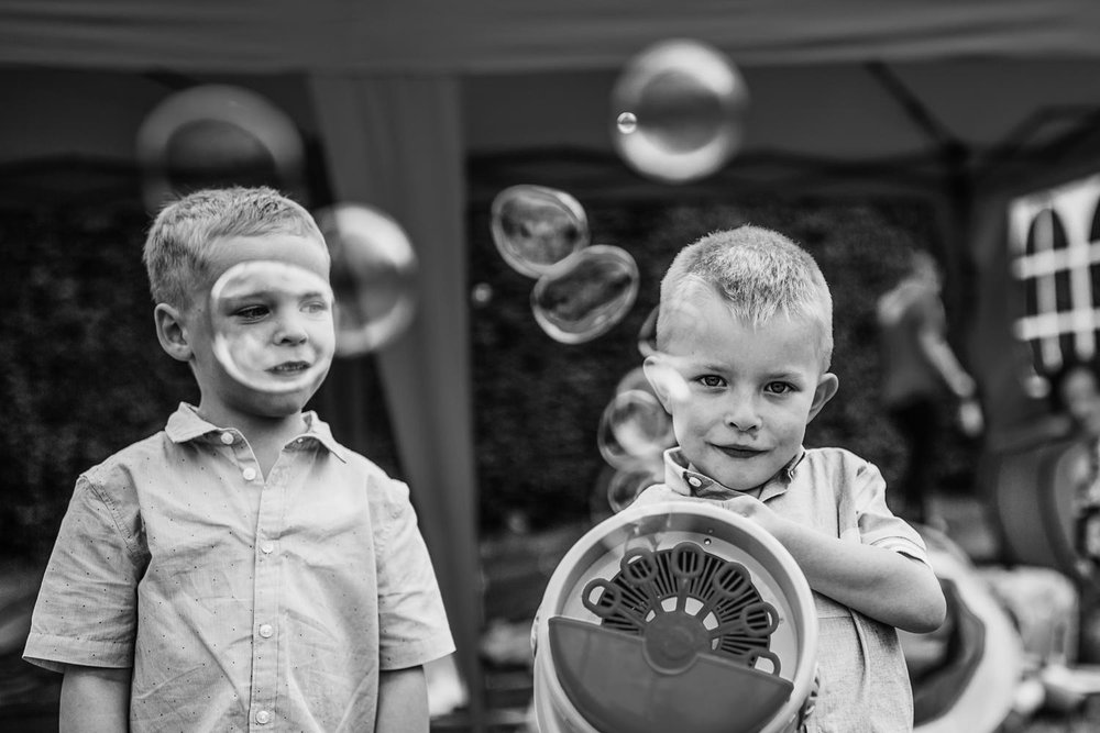 Two young boys play with a bubble machine during wedding reception