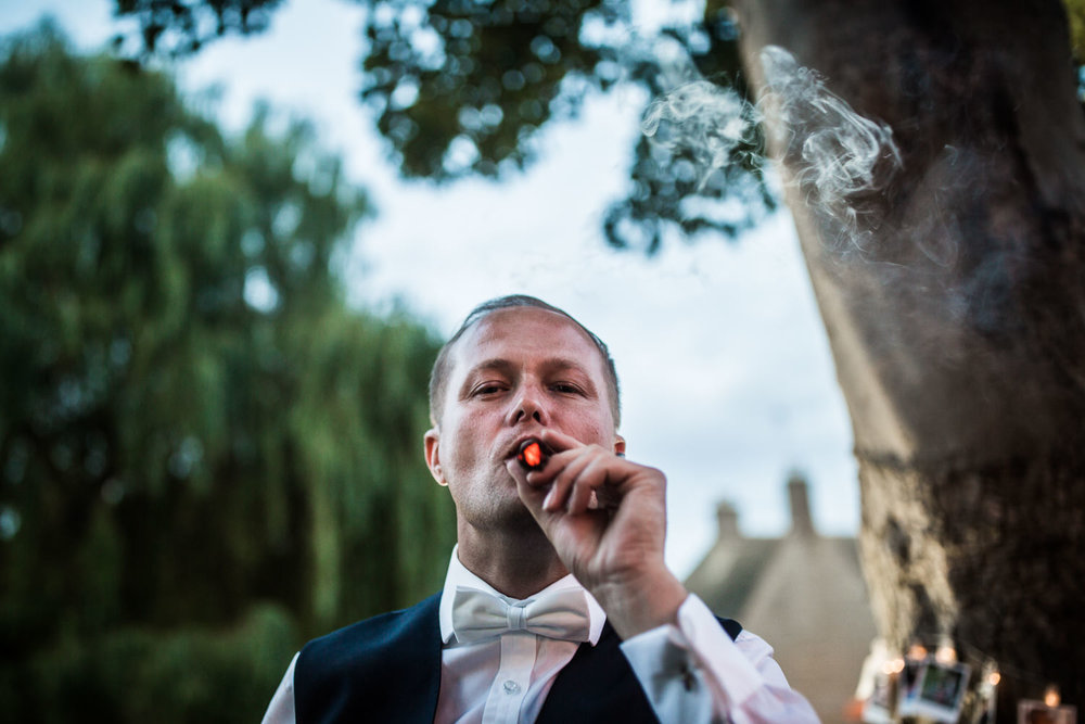 Satisfied Groom enjoys a cigar after his wedding breakfast