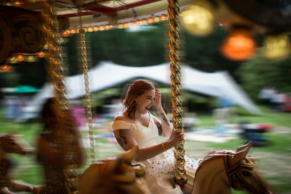 A Bride rides a gallopers carousel at Lanwades Hall, Newmarket.