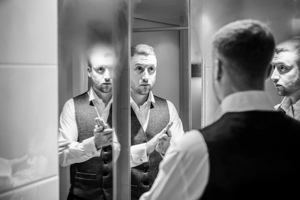 Groom applies aftershave in steamy hotel bathroom mirror.