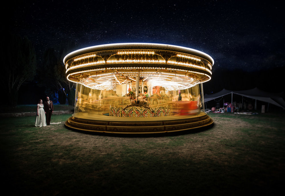 Traditional galloper carousel spins in a starlit setting as married couple look on at Lanwades hall, Newmarket, Suffolk