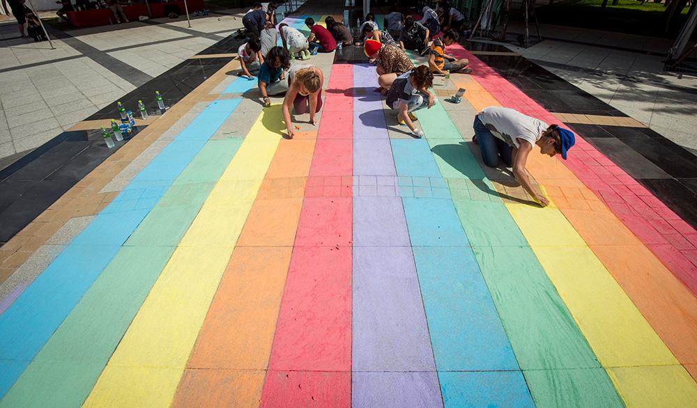 14 พ.ค., ณ ธรรมศาสตร์ท่าพระจันทร์ ทีมงานวาดรุ้งด้วยชอล์ก เริ่มจากอนุสาวรีย์ ฯพณฯ ปรีดี พนงยงค์ ไปยังเวทีเสวนาที่ร่วมแลกเปลี่ยนพูดคุยโดย น.ศ. LGBT    ©UNAIDS/UNESCO/A.Martin