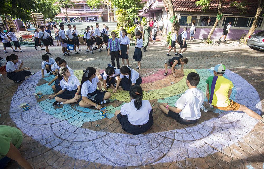 วาดรุ้งข้างประตูโรงเรียนมัธยมประชานิเวศน์ วันที่ 16 พค นักเรียนทุกคนได้เห็น บางคนยืนมองด้วยความสงสัย บางคนมาร่วมวาด   ©UNAIDS/UNESCO/A.Martin
