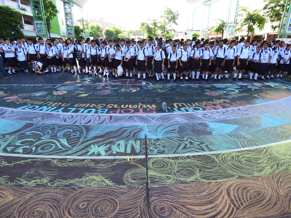 เกิน 2000 คนของนักเรียน รร.วัดนวลนรดิศยืนเข้าแถวหน้ารุ้งในวันแรกของการเปิดเรียน ท่านรอง ผอ. ให้การสนับสนุนโครงการ และ นร.ได้ฟังการรณรงค์ยุติการรังแกกลั่นแกล้งต่อ LGBT    ©UNAIDS/UNESCO/H.Nhan