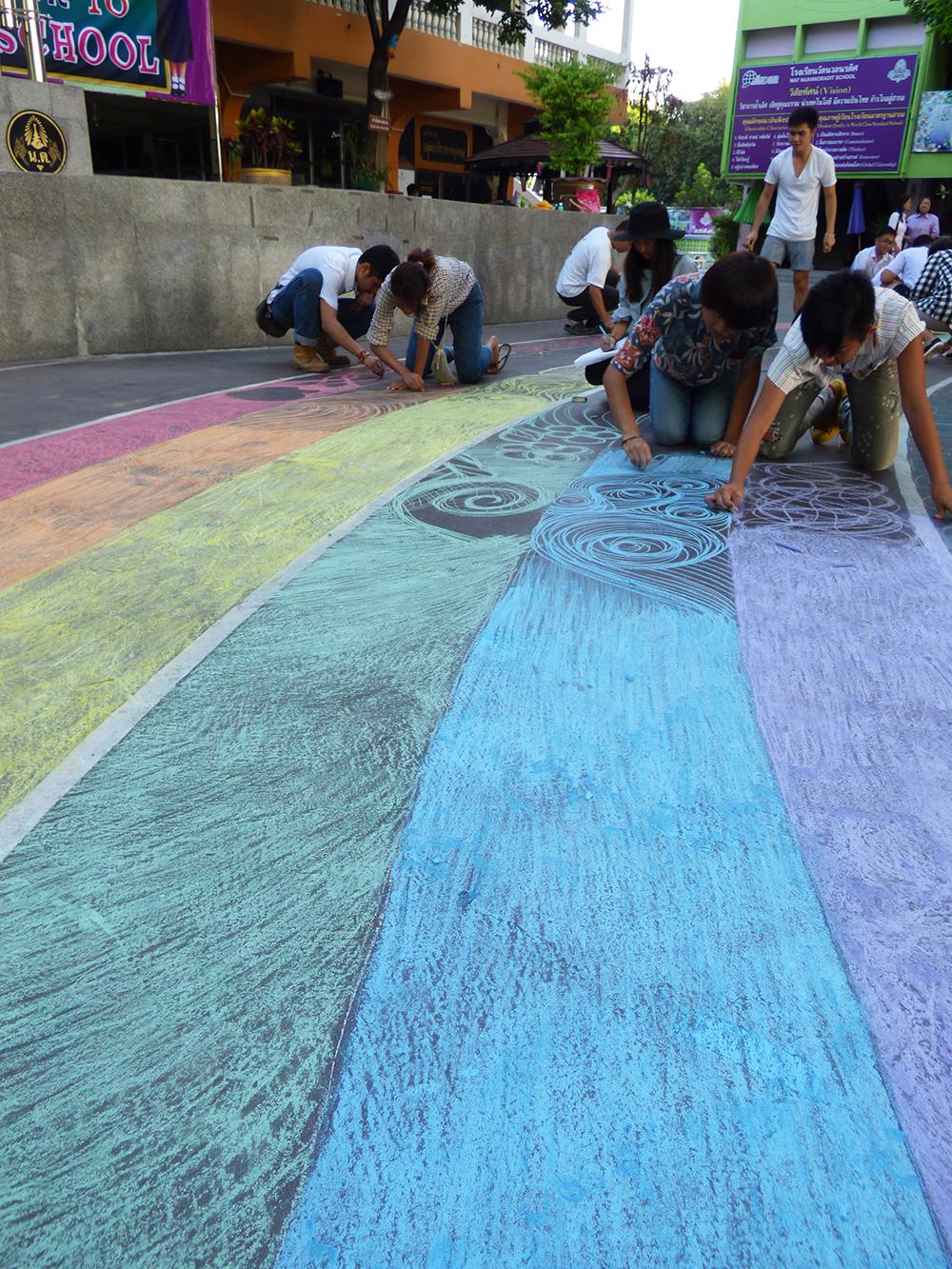 โครงการโรงเรียนสีรุ้งที่โร  งเรียนวัดนวลนรดิศ เริ่มด้วยการวาดรุ้งด้วยชอล  ์กสีแล้วเกิดเป็นงานศิลป์ รูปคลื่น, นก, กระทั่ง มังกร ถูกวาดลงบนรุ้ง