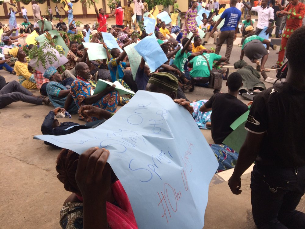 "Lagos federation protests threatened eviction of dozens of waterfronts in Lagos. On day 1 of protests, 13 October 2016, protesters lie in the street to demonstrate how the threatened evictions will cause loss of lives, shelter, and livelihoods. One sign reads ""destroy one slum, another springs up. #oururbanagenda."""