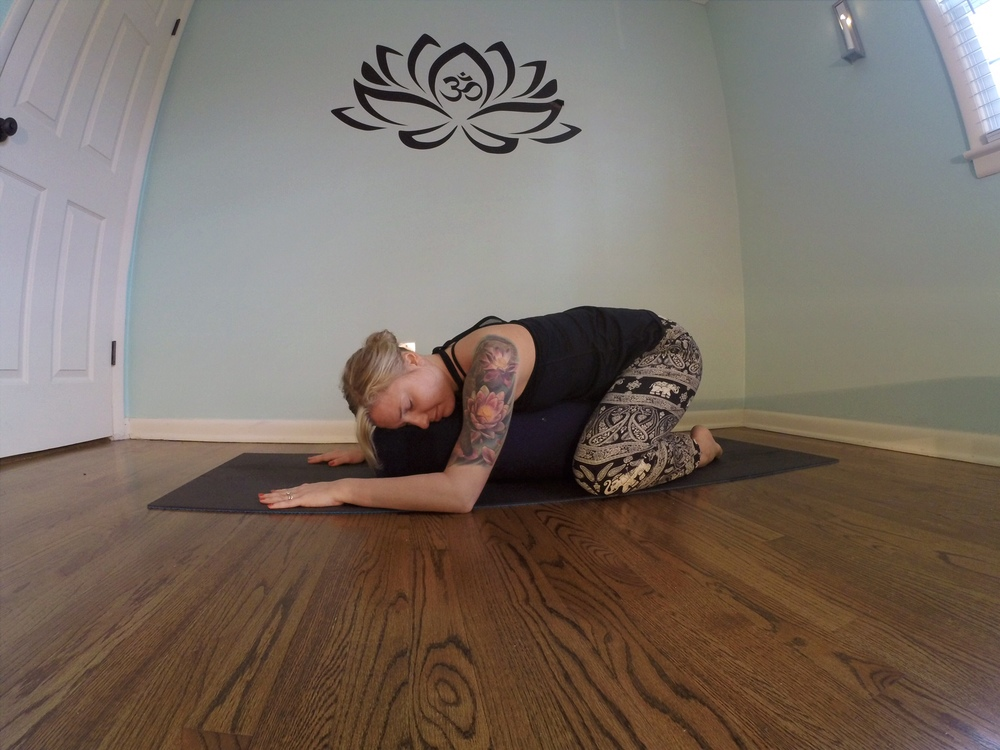 Restorative child's pose (balasana) with a bolster