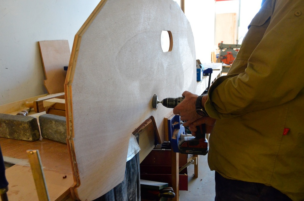Sanding the boomkin hole.  The two layers are slightly different sizes which gives a stepped outer edge which gives the bevel for planking.