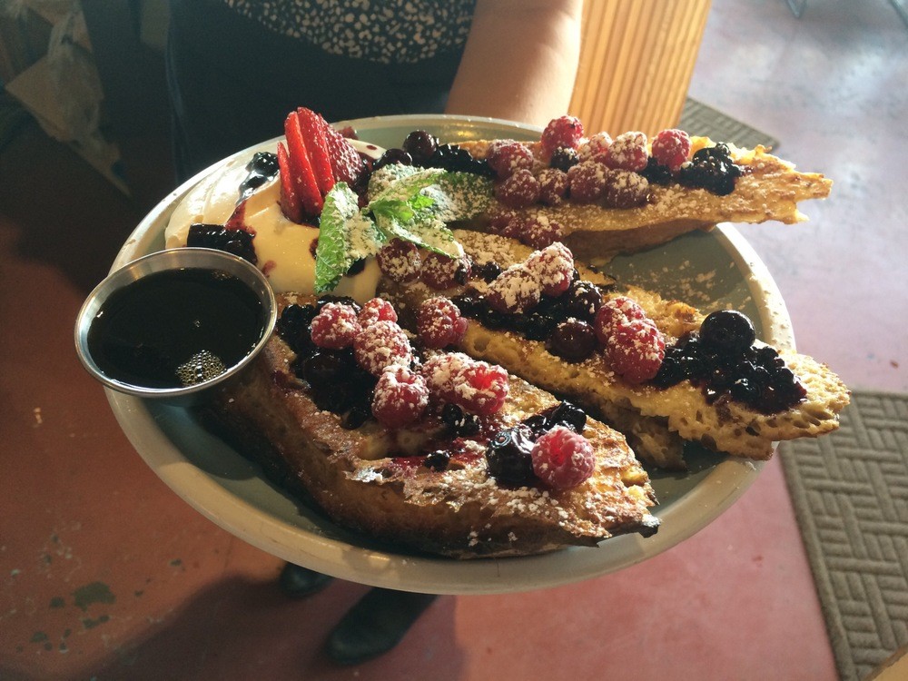 Crowd pleasing french toast from handmade Scorcher bread adorned with wild foraged summer berries, fresh whipped cream, aromatic mint, powdered sugar, and golden maple syrup.
