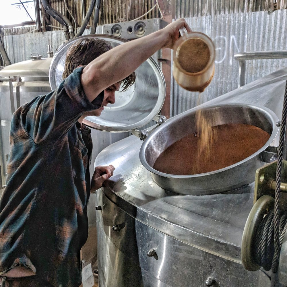 Brewer Sean Spiller adding mesquite to the mash tun at Jester King Brewery