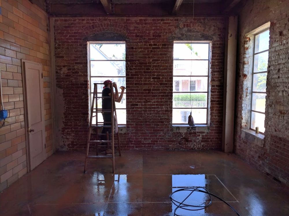 Here is a picture of Mack behind a ladder scraping the brick in the future cafe space.