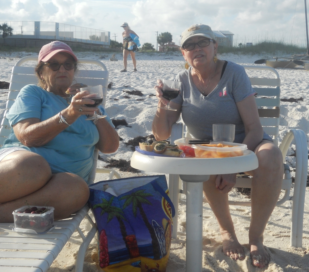 Peggy (right) & friend Jackie (left) savoring wine & a beach dinner