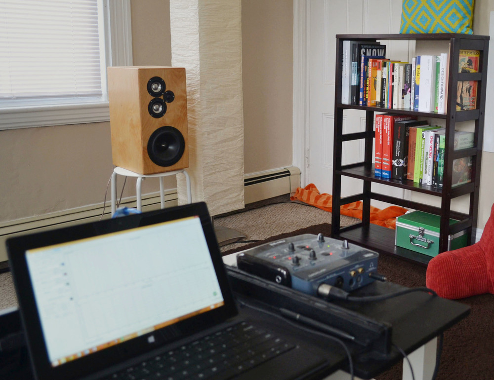 right speaker is next to a bookcase with actual books.