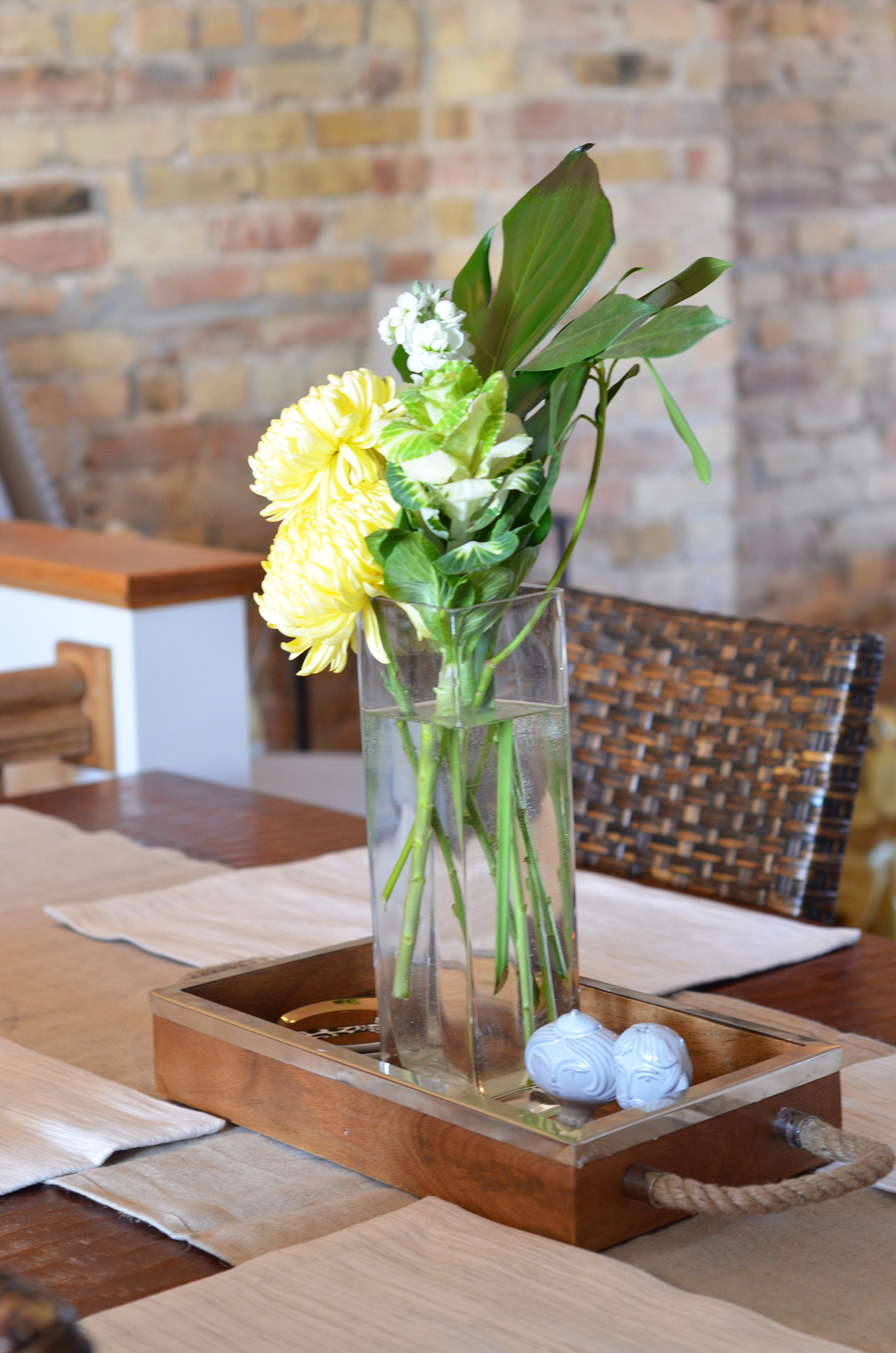 Floral centerpiece, a pop of yellow nicely compliments the wood table.