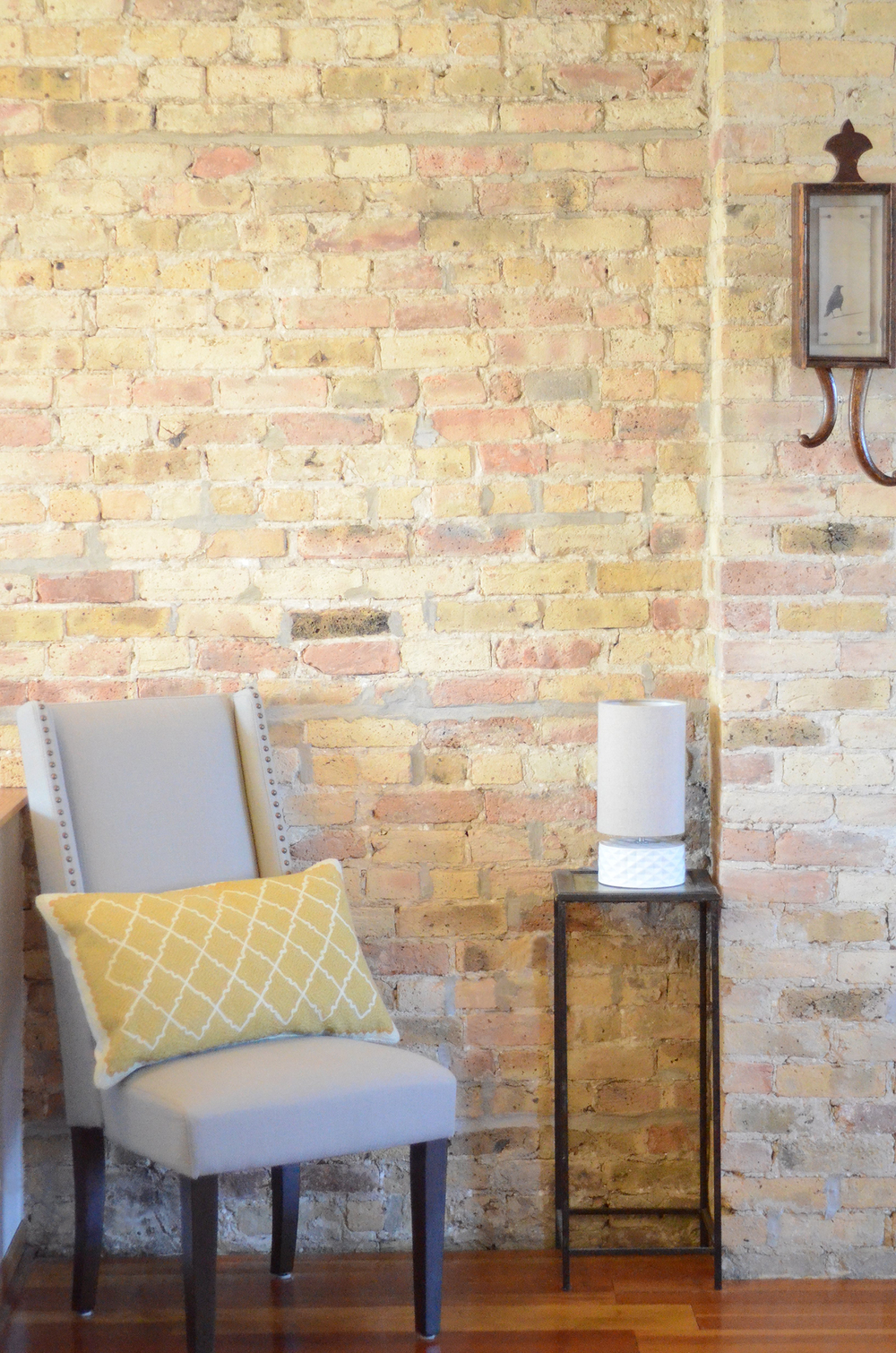 Accent chair up against an exposed brick wall. Simple and neutral.