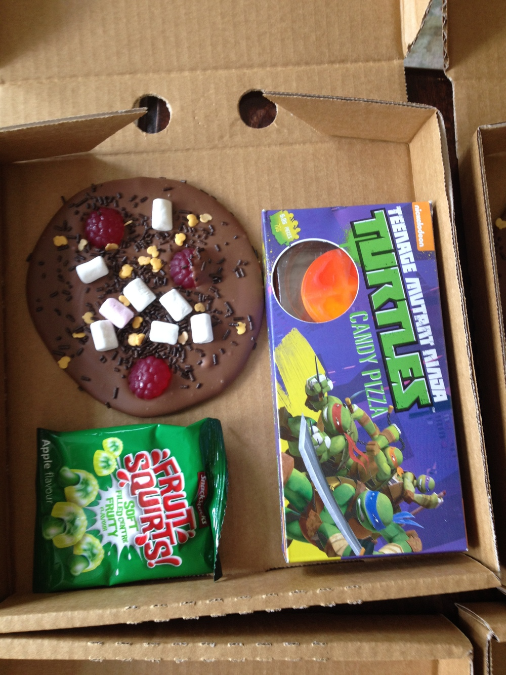 The contents of the lolly boxes, homemade Chocolate Pizza, Fruits quirts &  Ninja Turtle candy pizzas .