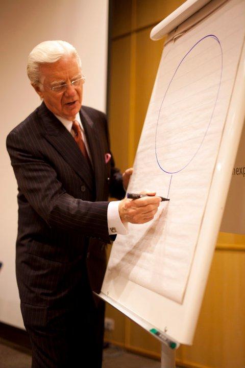Bob Proctor piirtämässä legendaarista tikku-ukkomallia perjantai-illan VIP-tilaisuudessa.
