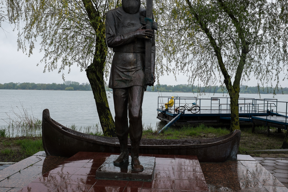 2014. A man fishes in the Danube at Vilkovo, near a statue commemorating early Lipovan settlers to the region. The Lipovans - Orthodox Old Believers - came to this corner of Ukraine after the schism of the Russian Orthodox Church, caused by the reforms of Patriarch Nikon in 1654. © Christopher Leigh