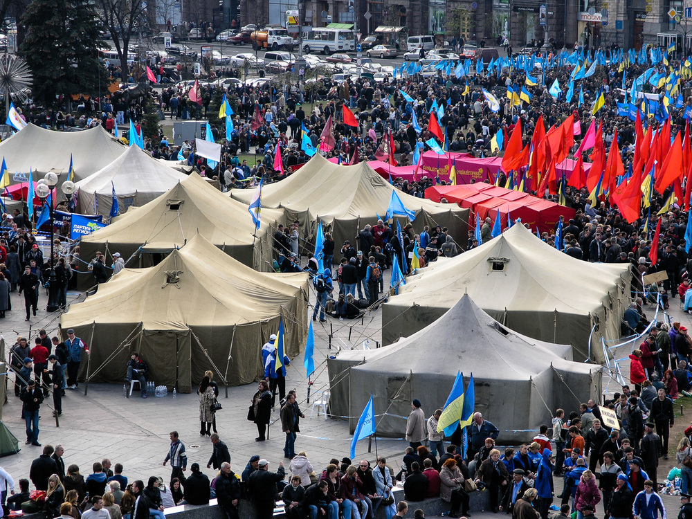 A political rally in Kiev's Independence Square. Since its independence from the USSR in 1991, political crises, from the Orange Revolution of 2004 to the Euromaidan uprisings of 2014, have rendered Ukraine's future uncertain. The red flags belong to the Ukrainian Communist Party. The blue flags belong to the Party of Regions.