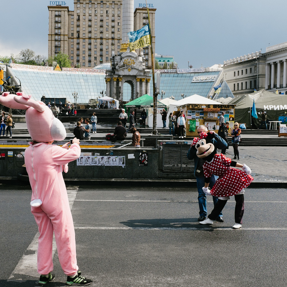 A tourist poses with workers dressed as cartoon characters on Kiev's Independence Square, April 2014.