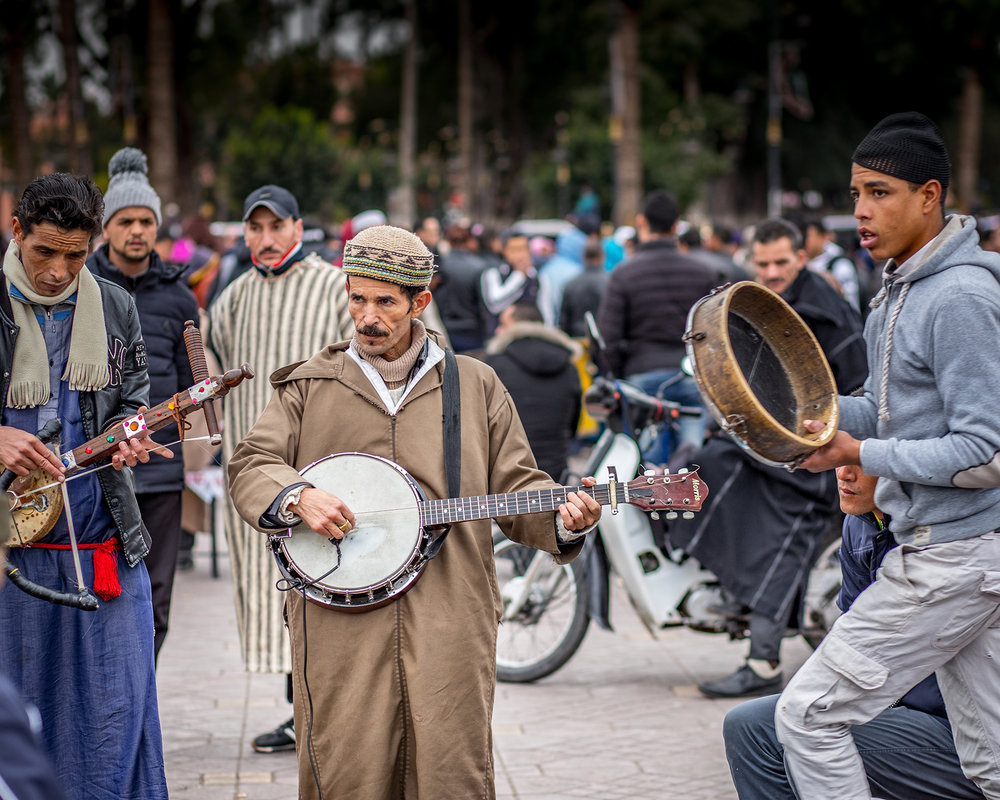 Moroccan street musicians play for tips in the market square.