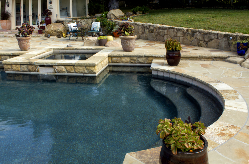 Curved steps following the contour of the pool's design create graceful entry into cool waters.  Light flagstone pairs well with white tile along pool's waterline; blending into black pebble aggregate finished pool.