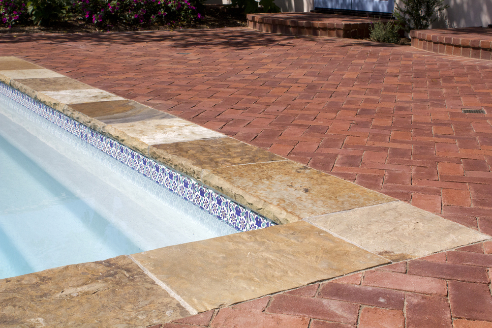 A mixture of stone materials (brick and flagstone) leading to pool's edge with set in decorative tile along the water line highlighting classic white plaster pool finish.