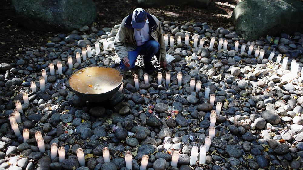 A man lights a candle in the National Aids Memorial grove in San Fransisco.