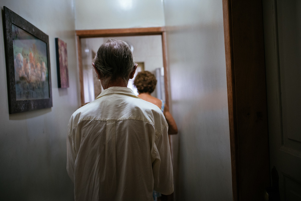 "Euracy Aguiar Prado, 80, and his wife, Edina Ferreira Prado, 70, walk though a hall in their home. ""What is our purpose on Earth?""  Mrs. Prado asked. ""To leave it better than we found it"". Rio de Janeiro, Brazil, 03-16-2015."