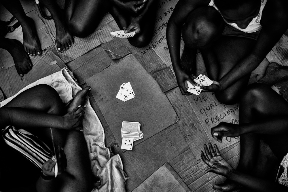 Homeless women play cards to pass the time.