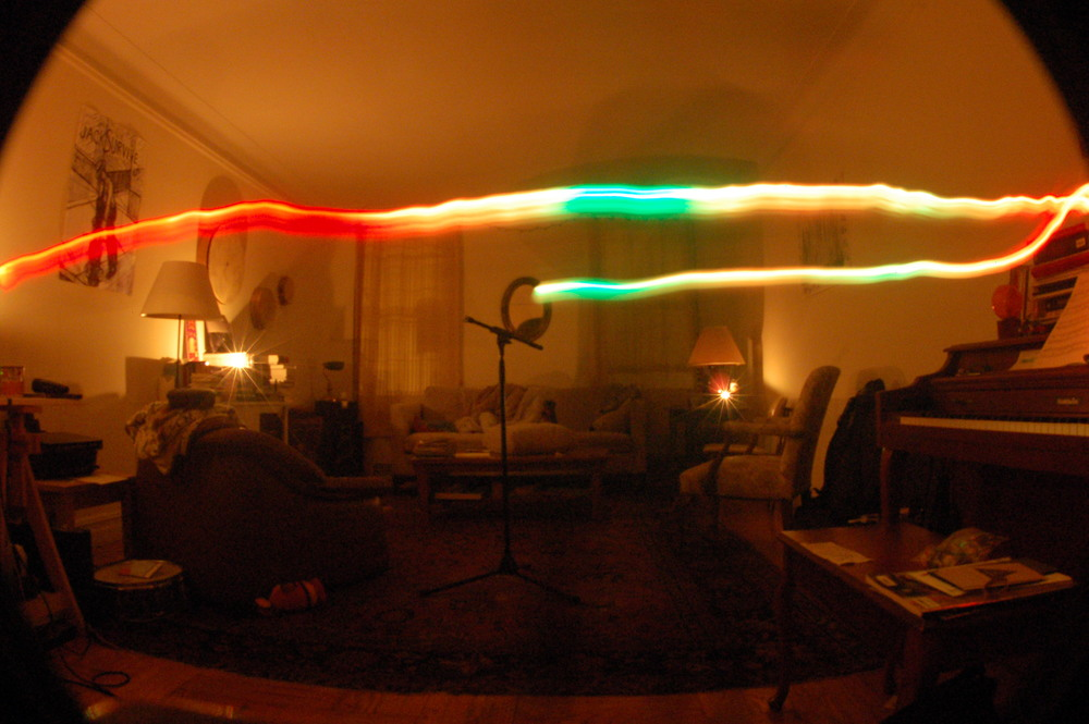 These next pictures were done with a tricolor LED. The green streaks are analogous to the absence or fading red light in the picture above - which is where there's a loss in volume. The red light in these pictures aims to represent the antinodes or where there's a higher amplitude, the green light the node, and the orange color represents the transition between the two points.