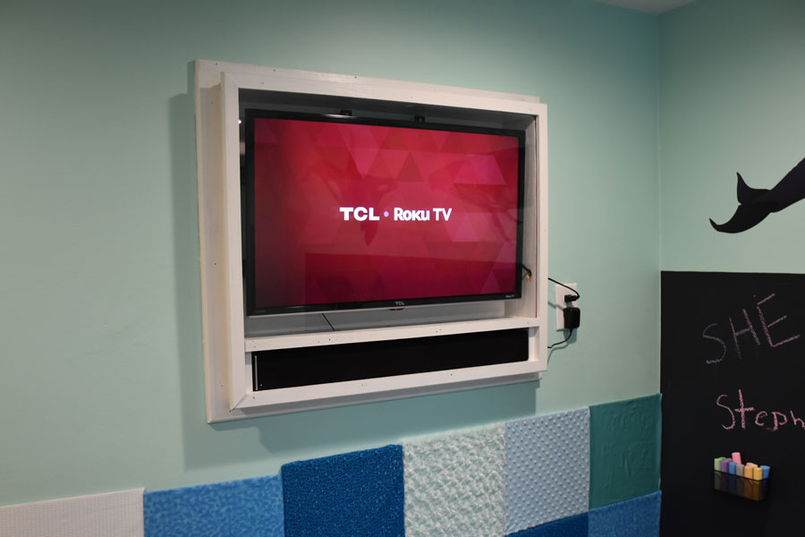 Recessed TV covered with plexiglass. Combination of smart TV and soundbar will give Landyn a calming environment when whale songs are streamed through the room