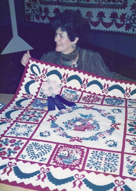 Elly holding Donna Collin's BlueRibbon-winning 8' block quilt made from Spoken Without a Word-1983. Donna first (to Elly' knowledge) miniaturized the blocks from Elly's first book, — and first to use Elly's mother-drawn Butterfly pattern (left of ribbon.)