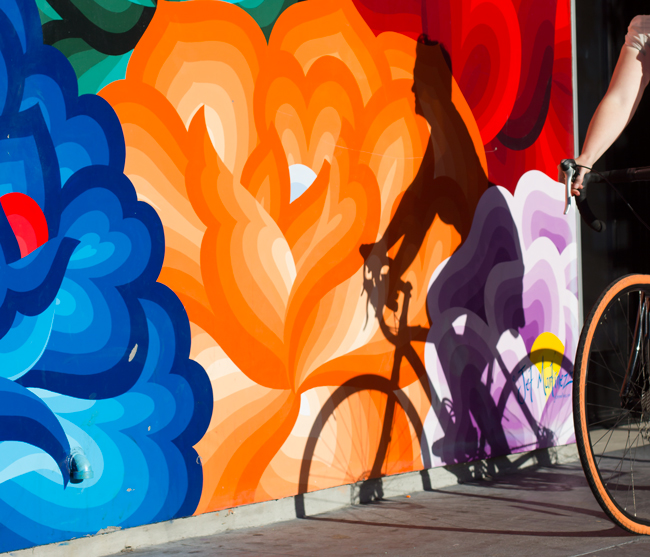 A woman rides a bikes near a mural on San Francisco's Valencia Street