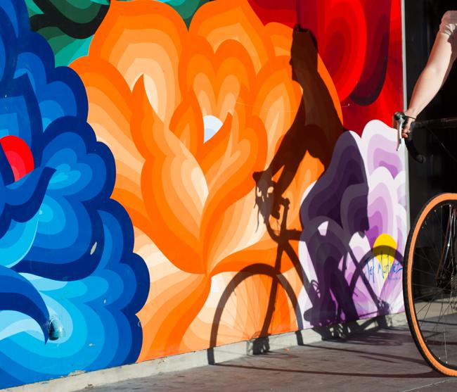 A woman rides a bikes near a mural on San Francisco's Valencia Street