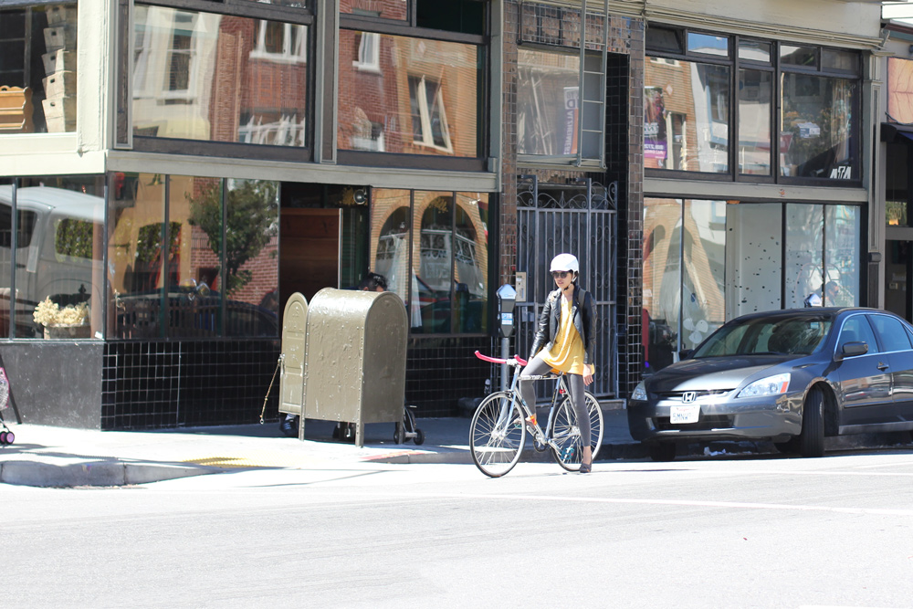 A fashionable woman rides her bike on Valencia Street in San Francisco.