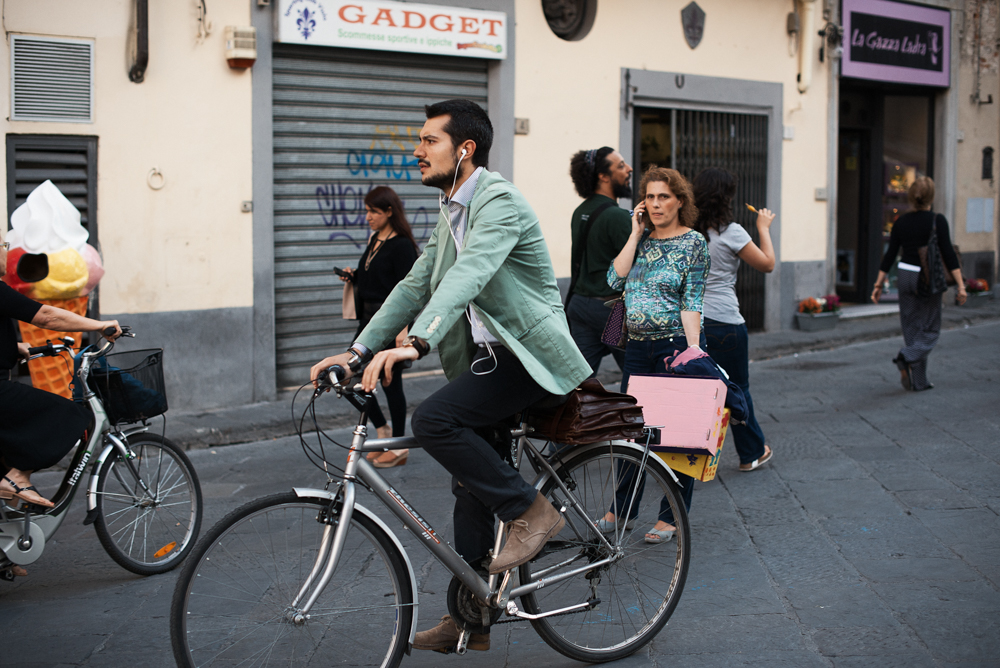 A well-dressed man rides a bike through the center of Florence, photo via Men In This Town blog.