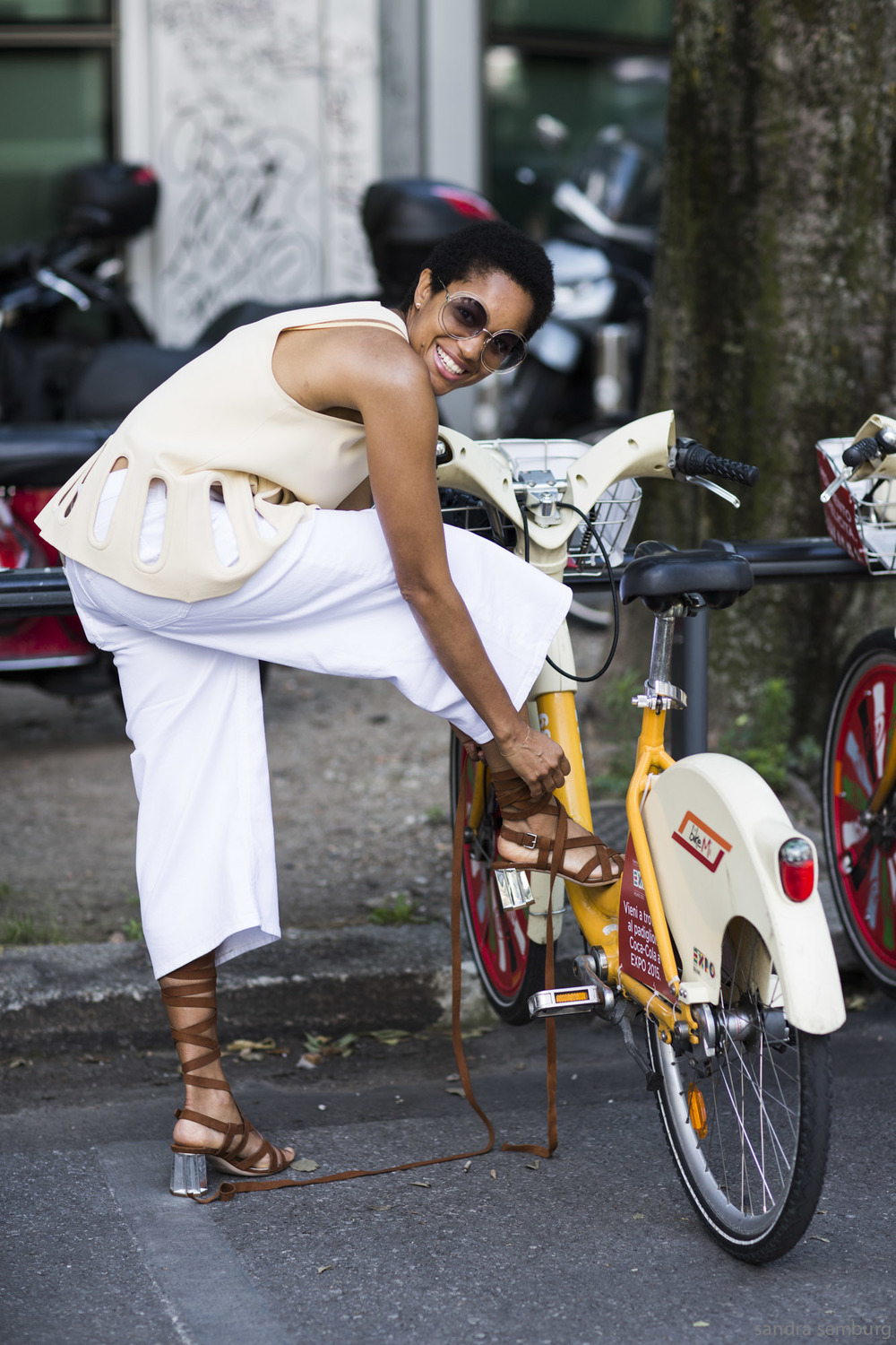 The radiant Tamu McPherson gets a leg up thanks to Milan's bike share during Fashion Week in 2015.