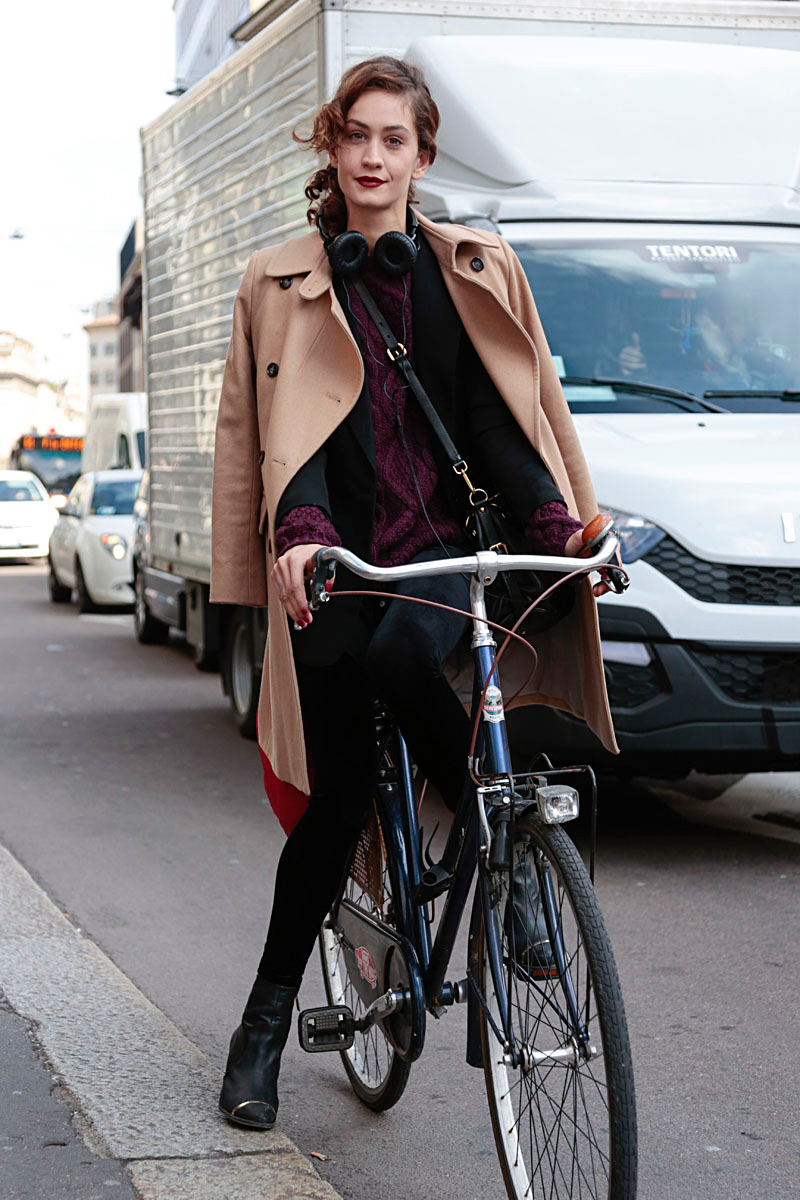 She's mastered next-level bike fashion by wearing her chic camel overcoat as a cape.