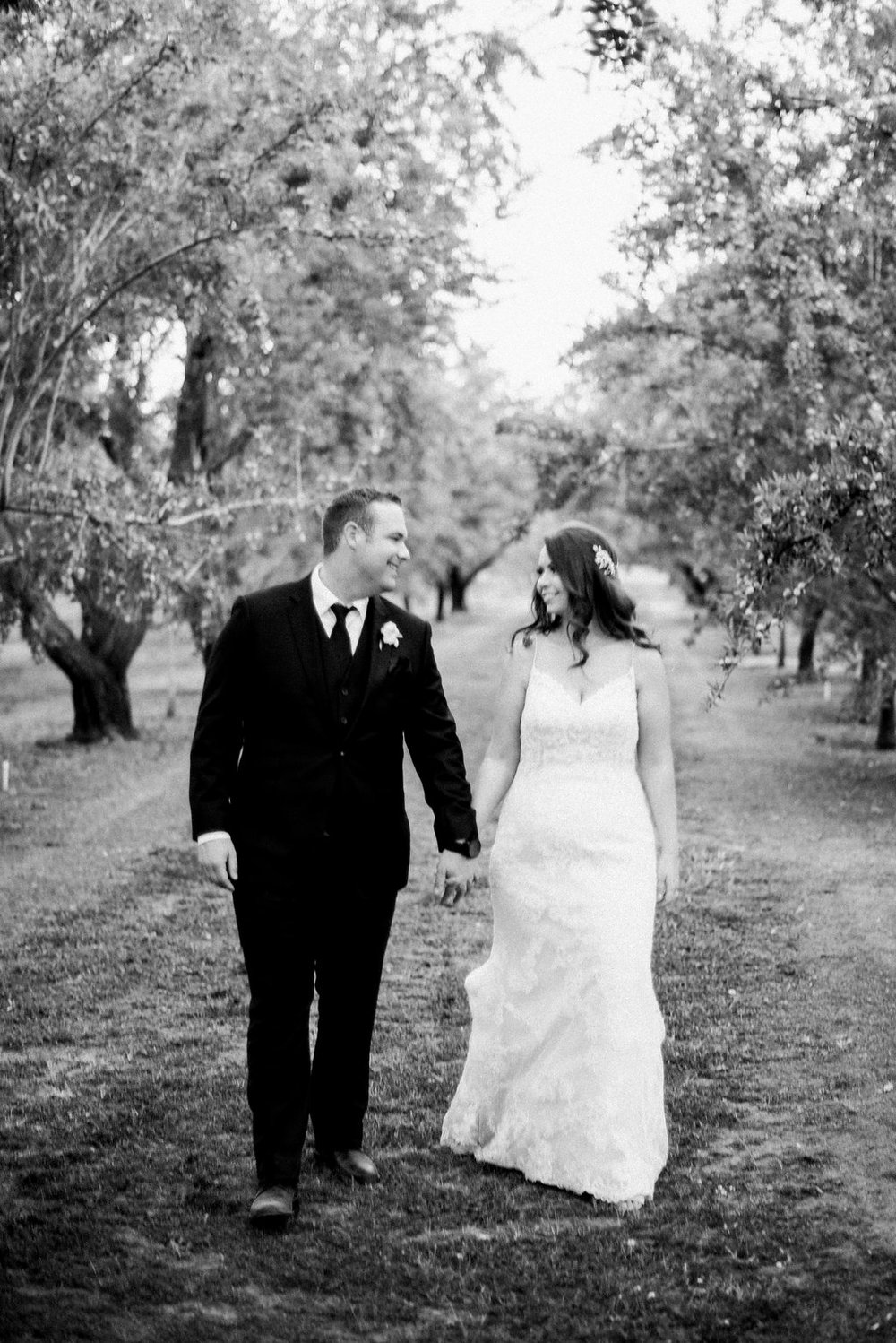 Shannon Rosan - Bride and Groom walking through almond orchard