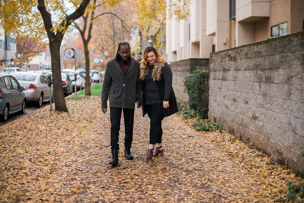 couple walking down sidewalk with fall leaves